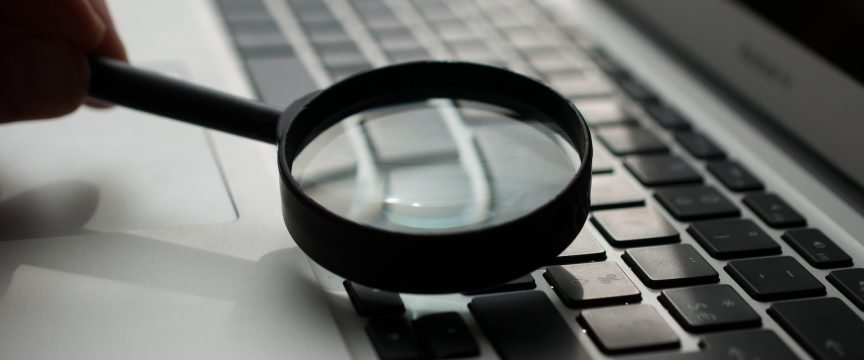 A magnifying glass on a laptop keyboard